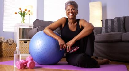 A woman with a yoga mat, stability ball and handweights