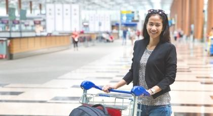 A smiling woman stands with a luggage trolley in an airport
