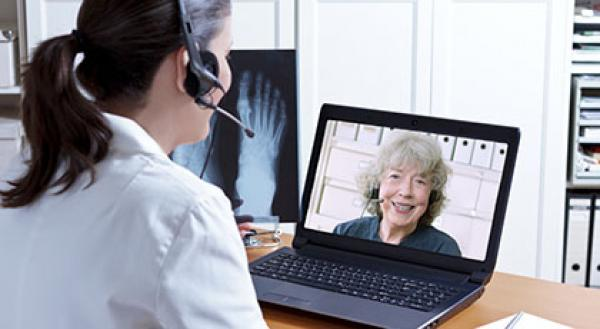 A physio takes part in a video call with a woman