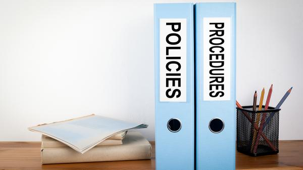 Desk scene with binders labelled 'Policies' and 'Procedures'