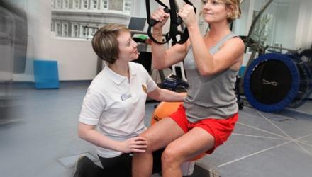 Physio guiding a woman through exercises