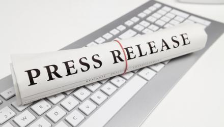 A rolled up newspaper saying 'press release' atop a keyboard
