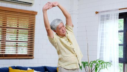 Man doing stretching exercises at home to alleviate pain