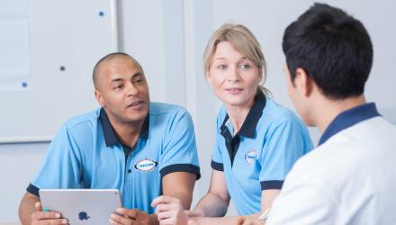 two support workers listening to a physio