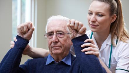 Physio assessing a stroke patient by lifting their arms