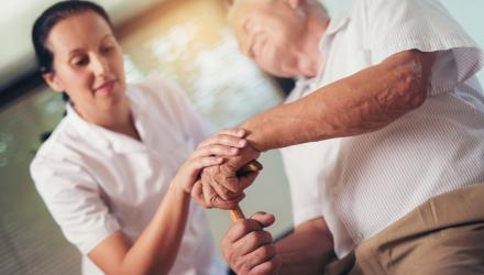 Physio holding hand of old man with walking stick