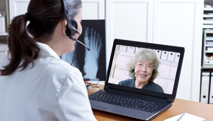 healthcare professional having a computer consultation with a patient